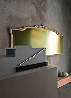 A gilt-frame hangs on a grey concrete wall.