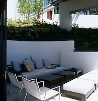 A large modern sofa with occasional tables and stools furnish a shady sunken seating area located below the bridge-like structure of the house