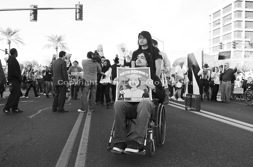 Mesa, Arizona, February 23, 2012 - As Republican candidates debated in the Mesa Arts Center, protesters including undocumented students, tea partiers, occupy movement members and Syrian president opponents, shouted slogans and held up signs and placards outside. In this photograph, Cesar Calderon, a DREAM Act supporter, participates in the protest against candidate Mitt Romney. Photo by Eduardo Barraza © 2012