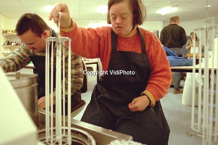 Foto: VidiPhoto..TIEL - Andersbegaafde medewerkers van cadeauwinkel Okee in Tiel oefenen vrijdag in de gloednieuwe kaarsenmakerij alvast met het maken van kaarsen. .Volgende week donderdag start de winkel, die cadeau-artikelen verkoopt gemaakt door verstandelijk gehandicapten, officieel met een eigen kaarsenfabriekje. Tot nog toe gebeurde het werk in een kleine ruimte in dagcentrum De Batouwe. Met de kaarsen wordt echter zoveel winst gemaakt, dat het .centrum dit succesvolle onderdeel gaat uitbreiden. Er gaan daar straks twaalf andersbegaafden aan de slag..