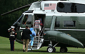 United States President Barack Obama (2nd L) salutes to a Marine as he walks towards the Marine One with daughter Malia (3rd L) and family friends prior to their departure from the White House August 24, 2012 in Washington, DC. According to a White House news release, Obama will spend the night at Camp David. .Credit: Alex Wong / Pool via CNP