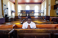 Worshipper in the Falmouth Parish Church of St. Peter the Apostle. The oldest public building in Falmouth. Jamaica Tourism.