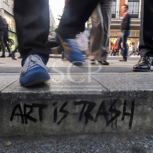 London, England. Street kerb with 'Art is Trash' graffiti, with pedestrian feet, in blue trainers and polished leather.