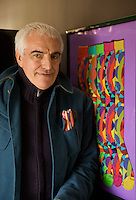 "Paolo Gagnara standing in front of a frame containing examples of his ""Gallo"" sock desgins"