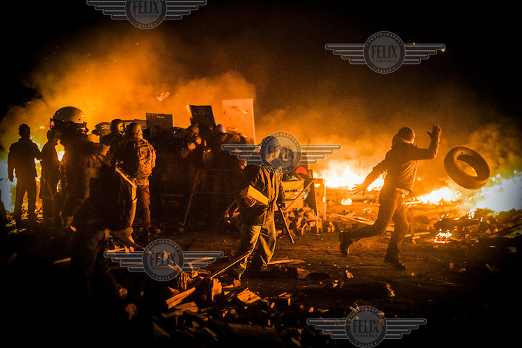A protester throws a tyre into the flames and other protesters lob projectiles at police lines on Maidan Nezalezhnosti (Independence Square), renamed EuroMaidan by protesters since November 2013. Protests against the government of President Viktor Yanukovych were sparked on 21 November 2014 by the Ukrainian government's decision to suspend preparations for the signing of an association agreement with the European Union that would have increased trade with the EU. Some believe that the U-turn came about as a result of pressure from President Putin of Russia who wants Ukraine to join a customs union with itself, Kazakhstan and Belarus. Russia offered 15 billion dollars of soft loans and reduced price gas to Ukraine at the same time as discussions with the EU were taking place. After weeks of protests and a number of deaths, Prime Minister Mykola Azarov and the entire cabinet resigned. Protesters are holding out, however, for President Yanukovych to resign and continue to occupy public buildings and squares to put pressure on the president. On 18 February, after Yanukovych's party scuppered a move to change the constitution to reduce the powers of the president, renewed fighting between protesters and police broke out and had cost the lives of around 80 people by Friday 21st February.