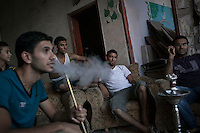 "In this Saturday, Aug. 16, 2014 photo, Palestinian youth are seen in a living room as they smoke ""narguile"" inside a house after it was damaged by artillery shelling during the ""Protective Edge"" Israeli military operation in Beit Hanoun neighborhood in Gaza City. After a five days truce was declared on 13th August between Hamas and Israel, civilian population went back to what remains from their houses and goods in Gaza Strip. (Photo/Narciso Contreras)"