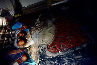 Children wake in their one-roomed shack in Site B, Khayelitsha, South Africa. (Photo by: Per-Anders Pettersson)