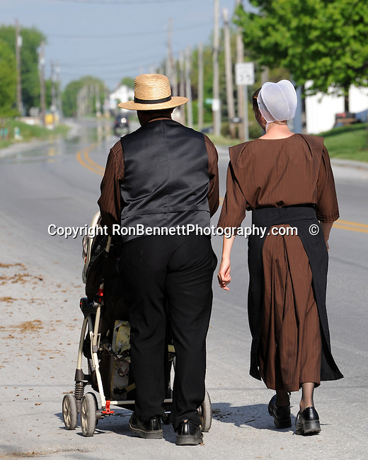 """A couple walk with their baby in Pennsylvania Dutch Country Amish Country in Lancaster County PA, Amish, Pennsylvania Dutch in Amish Country Lancaster County Pennsylvania, Amish, Horse and buggy with amish family on backroads of Pennsylvainia, buggy, amish family, buggy and horse, Commonwealth of Pennsylvania, Commonwealth of Pennsylvania, natives, Northeasterners, Middle Atlantic region, Philadelphia, Keystone State, 1802, Thirteen Colonies, Declaration of Independence, State of Independence, Liberty, Conestoga wagons, Quaker Province, Founding Fathers, 1774, Constitution written, Photography history, Fine art by Ron Bennett Photography.com, Stock Photography, Fine art Photography and Stock Photography by Ronald T. Bennett Photography ©, All rights reserved copyright Ron Bennett Photography.Com, FINE ART and STOCK PHOTOGRAPHY FOR SALE, CLICK ON  """"ADD TO CART"""" FOR PRICING,"""