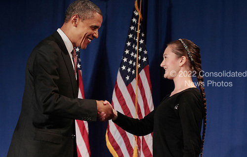 United States President Barack Obama shakes hands with Thomas Jefferson High School for Science and Technology senior Rebecca Hyndman before signing the America Invents Act at the school September 16, 2011 in Alexandria, Virginia. According to the White House, Hyndman received a patent in 2010 for her Under-Floor Storage invention, a simple idea that provides hidden storage space under the tiles of a kitchen or bathroom. The act reforms patent law so to give a patent to the first applicant rather than the first inventor and allows the woefully underfunded U.S. Patent and Trade Office to set and potentially keep its own fees..Credit: Chip Somodevilla / Pool via CNP