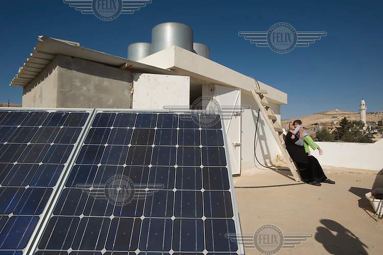 A family on the roof of their home in the Arab village of Darajat, in Israel's Negev desert. They are standing next to a photovoltaic solar panel which provides electricity to their house. The village is not connected to the national power grid, and solar power is being tested in some of the village's houses while the remainder rely on expensive and highly polluting diesel generators for their electricity.