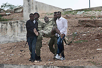 A soldier belonging to the Somali National Army is helped after being shot in the leg during the siege on Parliament House
