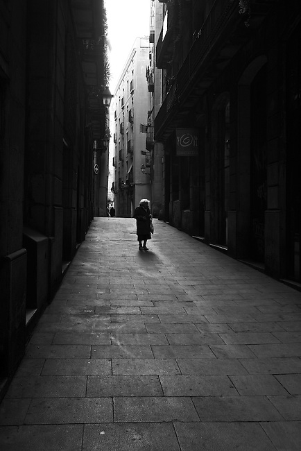 An old woman walks down an empty street in the Gothic Quarter in Barcelona, Spain. Feb. 17, 2009.
