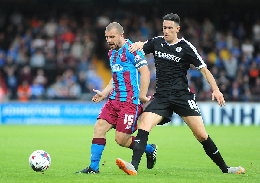 Scunthorpe United's Stephen Dawson shields the ball from Barnsley's Conor Wilkinson<br /> <br /> Photographer Andrew Vaughan/CameraSport<br /> <br /> Football - Capital One Cup First Round - Scunthorpe United v Barnsley - Tuesday 11th August 2015 - Glanford Park - Scunthorpe<br />  <br /> &copy; CameraSport - 43 Linden Ave. Countesthorpe. Leicester. England. LE8 5PG - Tel: +44 (0) 116 277 4147 - admin@camerasport.com - www.camerasport.com