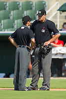 Home plate umpire Aaron Larsen (right) discusses a call with base umpire Aaron Roberts during a South Atlantic League game between the Hagerstown Suns and the Kannapolis Intimidators at Fieldcrest Cannon Stadium August 8, 2010, in Kannapolis, North Carolina.  Photo by Brian Westerholt / Four Seam Images