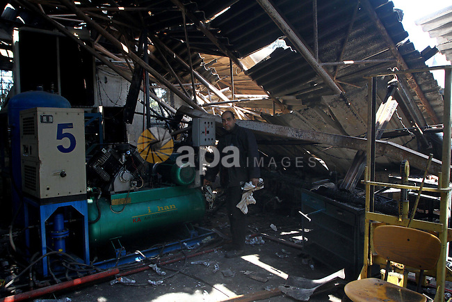 Palestinians observe the damage in a soft drinks factory after an explosion earlier on March 26, 2011 in the Zeitun neighbourhood of Gaza city. Despite Israel military said none of its forces were operating in the area, Palestinian security officials blame an Israeli tank shell. Photo by Ashraf Amra
