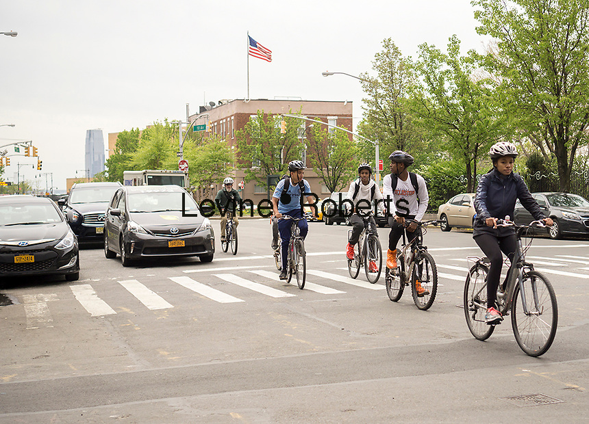 A pack of bicyclists travels up Tenth Avenue in New York amidst traffic on Thursday, April 28, 2016. (© Richard B. Levine)