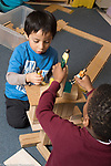 Education Preschool 3-4 year olds two boys playing with dolls on block structure they built