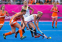 29 JUL 2012 - LONDON, GBR - Gaelle Valcke (BEL) of Belgium (in white) tries to avoid a tackle from Lidewij Welten (NED) of Netherlands   during their women's London 2012 Olympic Games Preliminary round hockey match at the Riverbank Arena in the Olympic Park in Stratford, London, Great Britain (PHOTO (C) 2012 NIGEL FARROW)