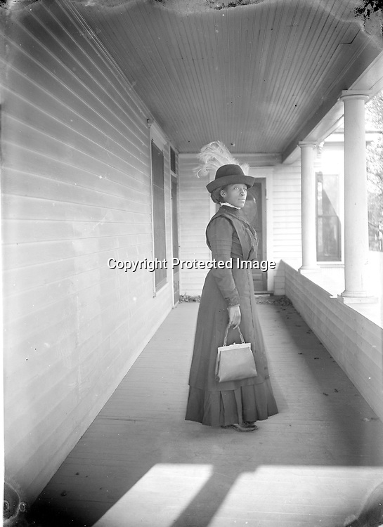 ELEGANT YOUNG WOMAN. Even without a studio, John Johnson endeavored to offer his subjects multiple portraits, altering poses, accessories, and solo versus group shots. Various photographs show this woman with and without her plumed hat and leather purse, sitting and standing, in profile and straight on (also see image LB002.) But all three views convey her strength and dignity.<br /> <br /> Photographs taken on black and white glass negatives by African American photographer(s) John Johnson and Earl McWilliams from 1910 to 1925 in Lincoln, Nebraska. Douglas Keister has 280 5x7 glass negatives taken by these photographers. Larger scans available on request.