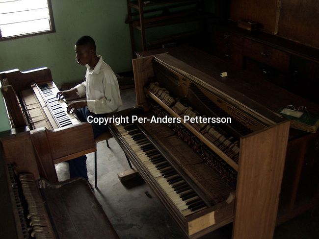 dimuinst00012 Musical instruments. Kiseme Eric, age 18, is playing the piano at the school for the blind on February 28, 2002 in central Kinshasa, Congo. This is his first ever getting an education as his parents kept him in their house for many years. He is teached by Mr. Gervais Mpidi, a piano teacher at the school. Mr. Mpidi also has to pick up and drop the students every day, as there's no transport. .©Per-Anders Pettersson/iAfrika Photos.