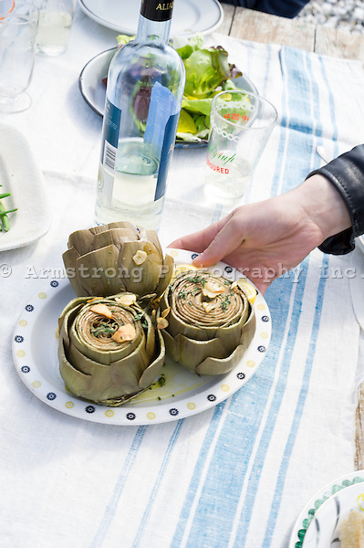 Closeup of an outdoor meal scene at a picnic table. A hand reaching for a plate of artichokes topped with sliced garlic, herbs, and garnished with lemon, bottle of white wine, and a green salad.
