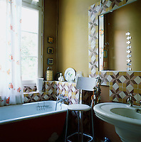 The bathroom has a traditional feel with mustard coloured walls and Victorian style bath and hand basin