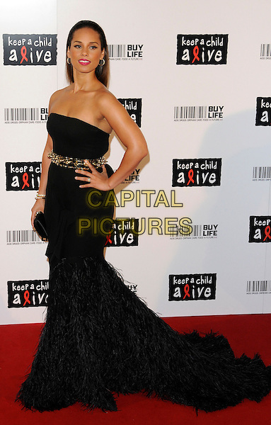 Alicia Keys .Arrivals at the Keep A Child Alive - Black Ball held at the Roundhouse, Chalk Farm Rd. London, England, UK, .June 15th, 2011..full length strapless black long maxi dress gown hand on hip side train  gold belt waistband  feathers feather clutch bag .CAP/CAN.©Can Nguyen/Capital Pictures.