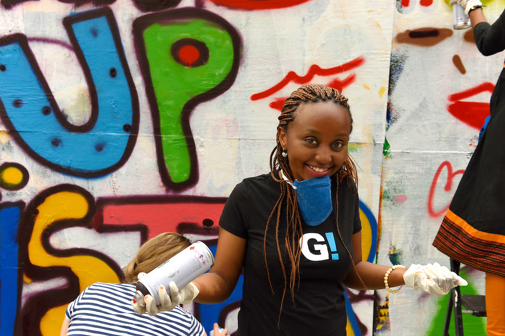 One of the girls posing for the camera with can of spray paint in hand.