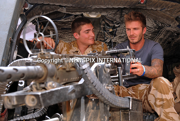 "DAVID BECKHAM.being shown the mounted Heavy Machine Gun on an Army Lynx helicopter by Lance Corporal Chandler, 9 Army Air Corps..David Beckham paid a surprise goodwill visit to UK and US troops in Camp Bastion. He met with hundreds of soldiers and gave away signed England shirts and memorabilia. He was, he said, 'overwhelmed' by the stories of courage he heard..Beckham arrived on Friday night on a Royal Air Force C17 aircraft, stepping off into 45 degree heat in body armour and helmet..After a night's sleep, he ate breakfast in the cookhouse, moving from table to table signing autographs and having photographs taken_Camp Bastion, Helmand Province, Afghanistan_22/05/2010.Photo Credit: ©LLoyd_Newspix International..**ALL FEES PAYABLE TO: ""NEWSPIX INTERNATIONAL""**..PHOTO CREDIT MANDATORY!!: NEWSPIX INTERNATIONAL..IMMEDIATE CONFIRMATION OF USAGE REQUIRED:.Newspix International, 31 Chinnery Hill, Bishop's Stortford, ENGLAND CM23 3PS.Tel:+441279 324672  ; Fax: +441279656877.Mobile:  0777568 1153.e-mail: info@newspixinternational.co.uk"