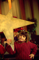Child age 8 holding the Holy star during Christmas pageant.  Western Springs  Illinois USA