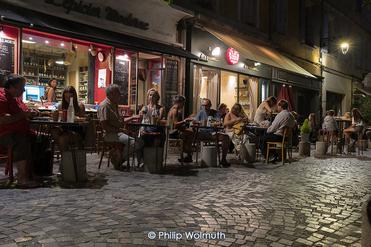 Diners eat at restaurants in a square in Arles, France.