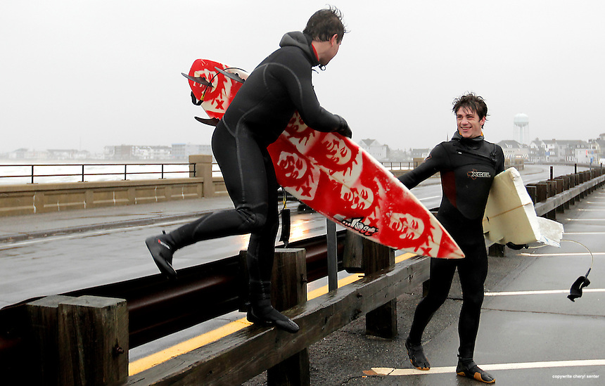 Surfers, from left, Colin Somogie of S.Hampton and Pat Losik of Rye, head back to their vehicles after riding the high waves in Hampton, N.H.,  Sunday, Dec. 12,  2010.  A strong wave snapped Losik's board in half.  (Portsmouth Herald Photo Cheryl Senter)