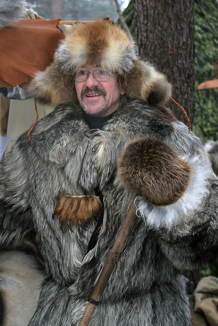 Market stall holder in a wolf skin coat with a bear paw on his chest, traditional craft market, Jokkmokk. Sweden. Size to A4