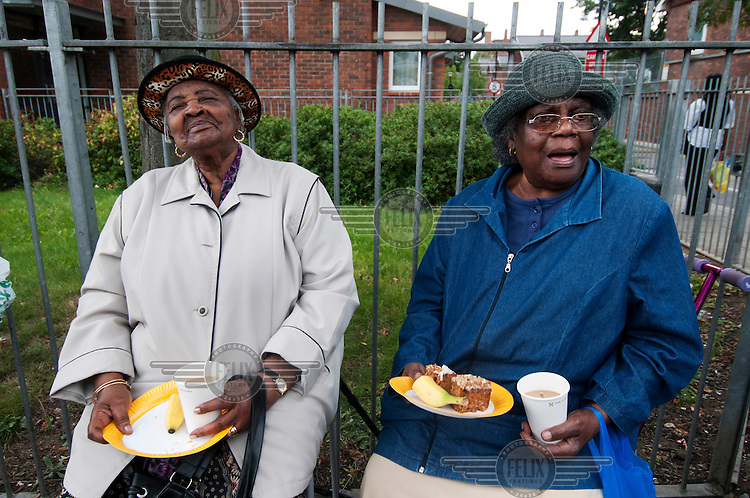 Two elderly women sit with plates of food at a street party on Clarence Road in the London Borough of Hackney; held a week after the area was the scene of rioting and looting...