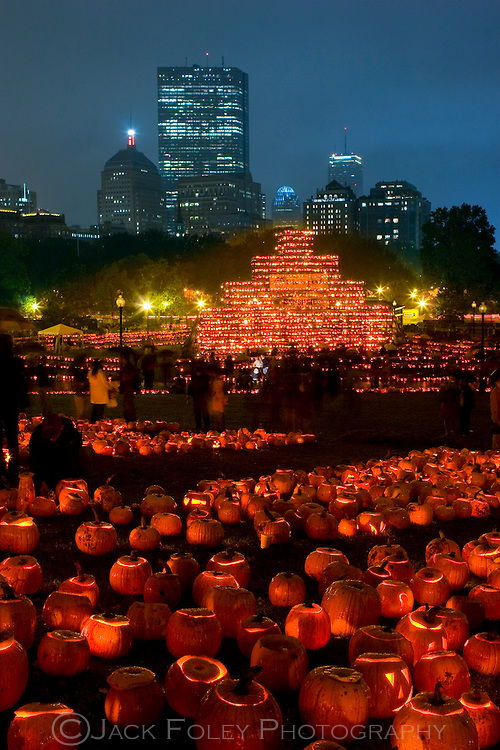 Jack-o-lanterns lit and stacked high on the Boston common with the city in the background.