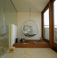 An Eero Aarnio bubble chair is suspended from the ceiling of the glassed-in garden room which opens on to the roof terrace