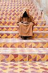 A hooded man sits on colorful steps, Essaouira, Morocco