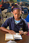 Black female second grader with braids in her hair and wearing a uniform reads at her desk in schoolroom.