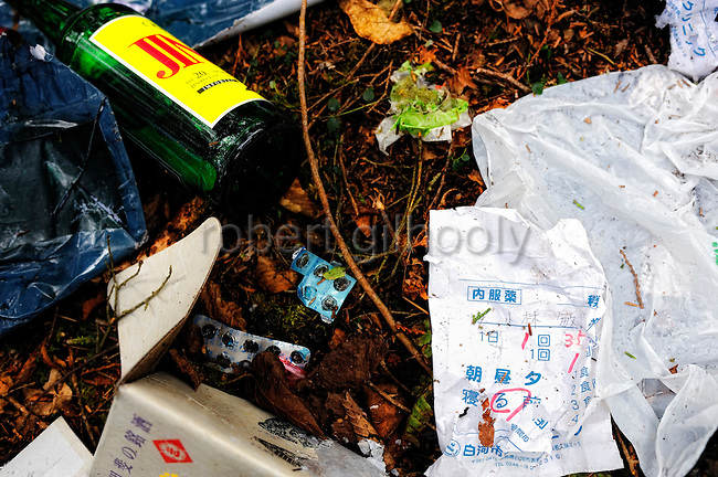 A variety of items, including clothes, empty liquor bottles and the empty packs of prescription pills with the prescription, are scattered near the base of a tree in Aokigahara Jukai, better known as the Mt. Fuji suicide forest, which is located at the base of Japan's famed mountain west of Tokyo, Japan. ..