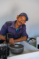 Africa, Madagascar, Ambositra city. Man polishing minerals for sale.