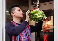 Nederland Amsterdam 2018. Chinees Nieuwjaar viering. In Amsterdam Chinatown wordt twee keer per jaar Nieuwjaar gevierd : op de eerste winkeldag na 1 januari en tijdens het officiele Chinese Nieuwjaar , dat een paar weken later plaatsvindt. Tijdens de viering van Chinees Nieuwjaar worden er leeuwendansen opgevoerd . Man hangt krop sla voor de leeuw op bij restaurant Nam Kee.  Foto Berlinda van Dam / Hollandse Hoogte