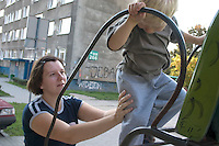 Mom giving support to son climbing park slide ages 28 and 3. Communist built Blok house. Balucki District Lodz Central Poland