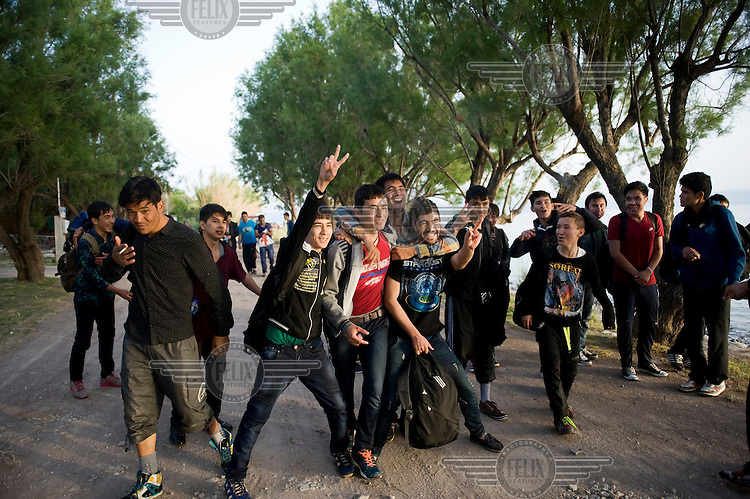 A group of Afghan teenagers celebrate after their boat landed on the beach of Skala Sykaminias on the Greek island of Lesbos. Every day hundreds of refugees, mainly from Syria and Afghanistan, are crossing in small overcrowded inflatable boats the 6 mile channel from the Turkish coast to the island of Lesbos in Greece. Many spend their life savings, over $1,000, to buy a space on these boats.