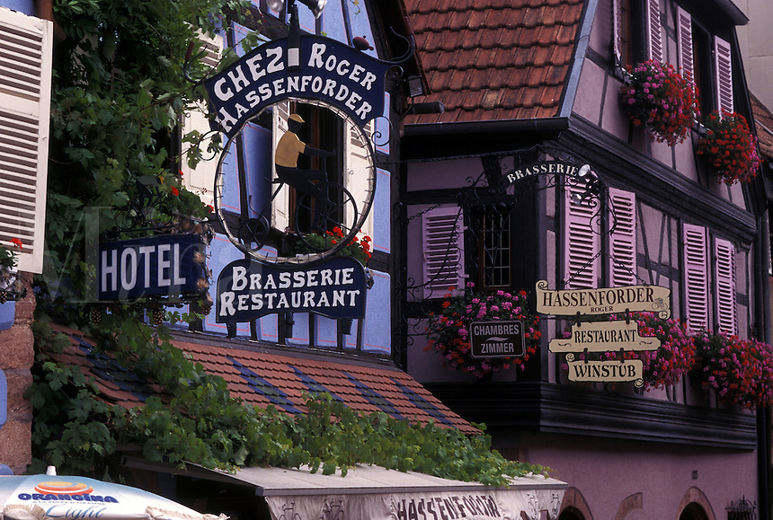 France, Alsace, Kaysersberg, Haut-Rhin, Europe, wine region, Outdoor café along a narrow cobblestone pedestrian street surrounded by half-timbered buildings in the picturesque village of Kaysersberg in the wine region of Alsace.