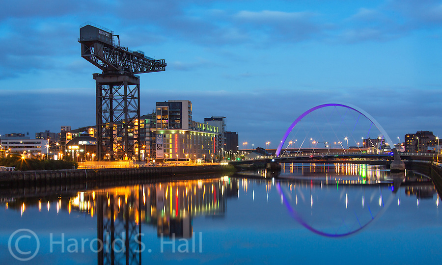 The purple illuminated Millennium Bridge spans the Clyde River in Glasgow Scotland.  In contrast to this very modern bridge, to the left is an old large crane used in heavy industry.