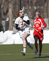 Boston College defender Claire Blohm (26) brings the ball forward. Boston University attacker Danielle Etrasco (13) drops off to avoid offsides..Boston College (white) defeated Boston University (red), 12-9, on the Newton Campus Lacrosse Field at Boston College, on March 20, 2013.