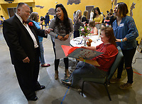 NWA Democrat-Gazette/ANDY SHUPE<br /> Greg Williams (left) of Springdale cracks a joke Friday, Feb. 9, 2018, as he gives his wife, Linda, a Valentine's Day Card as volunteers Kat Arteaga (center left), and Izzy Jacobo (right) laugh as Linda has her hair done before the start of the Night to Shine, a prom night for people with special needs ages 14 and older, at Cross Church in Springdale. The event, which is sponsored by the Tim Tebow Foundation, features hair and makeup assistance, limousine rides, a dinner and dancing.