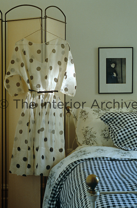 A black and white print and a polka dot dress hang above a rustic wrought-iron bed in this bedroom