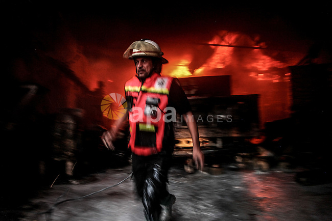 Palestinian firefighters try to extinguish fire from  soap factory that caught fire moments after it was hit by an Israeli airstrike in Gaza City August 10, 2014. Palestinian and Israeli negotiators on Sunday said they had accepted an Egyptian proposal for a new 72-hour truce with Israel, clearing the way for a possible resumption of talks on a long-term cease-fire arrangement in the Gaza Strip. Photo by Ezz Zanoun