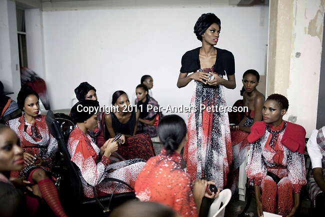 JOHANNESBURG, SOUTH AFRICA - FEBRUARY 19: Adebisi Sowemimo, a Nigerian Model, stands among other models before a show with the designer David Tlale, at his studios at the Joburg Fashion Week on February 19 2011, in Johannesburg, South Africa. David Tlale, is an award winning designer and one of South Africa's finest designers, dressing celebrities and others in couture with elegance and high quality material. He held his show at the Mandela Bridge in downtown Johannesburg. A logistical nightmare, the bridge was closed and turned into a  catwalk at midnight with hundreds of people watching the show. 92 models, one for each of Nelson Mandela's years walked the 285 meter bridge, maybe the longest catwalk in the world. South African top designers with showed their 2011 Autumn & Winter collections during the 5 day event. (Photo by Per-Anders Pettersson)